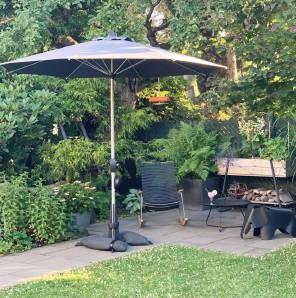 Baser Sonnenschirmständer Sonnenschirm Garten Ecke Rasen Fliesen Idylle gemütlich