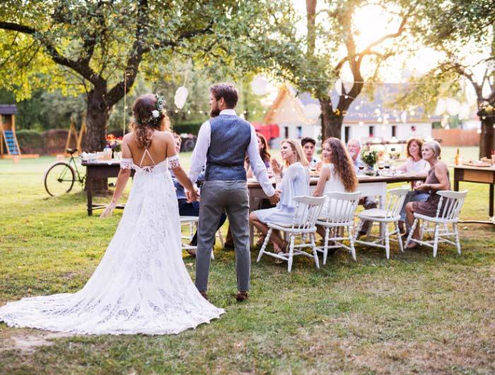 Bride and groom at backyard wedding with guests