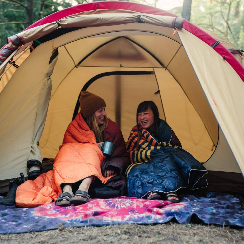 Two women camping with Rumpl blankets