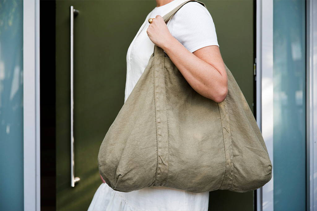 Model holds Frankie Linen Bag while standing in front of a door.