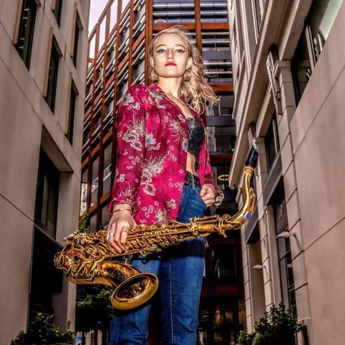 UK Saxophonist Emma Rawicz holding a tenor saxophone mark vi