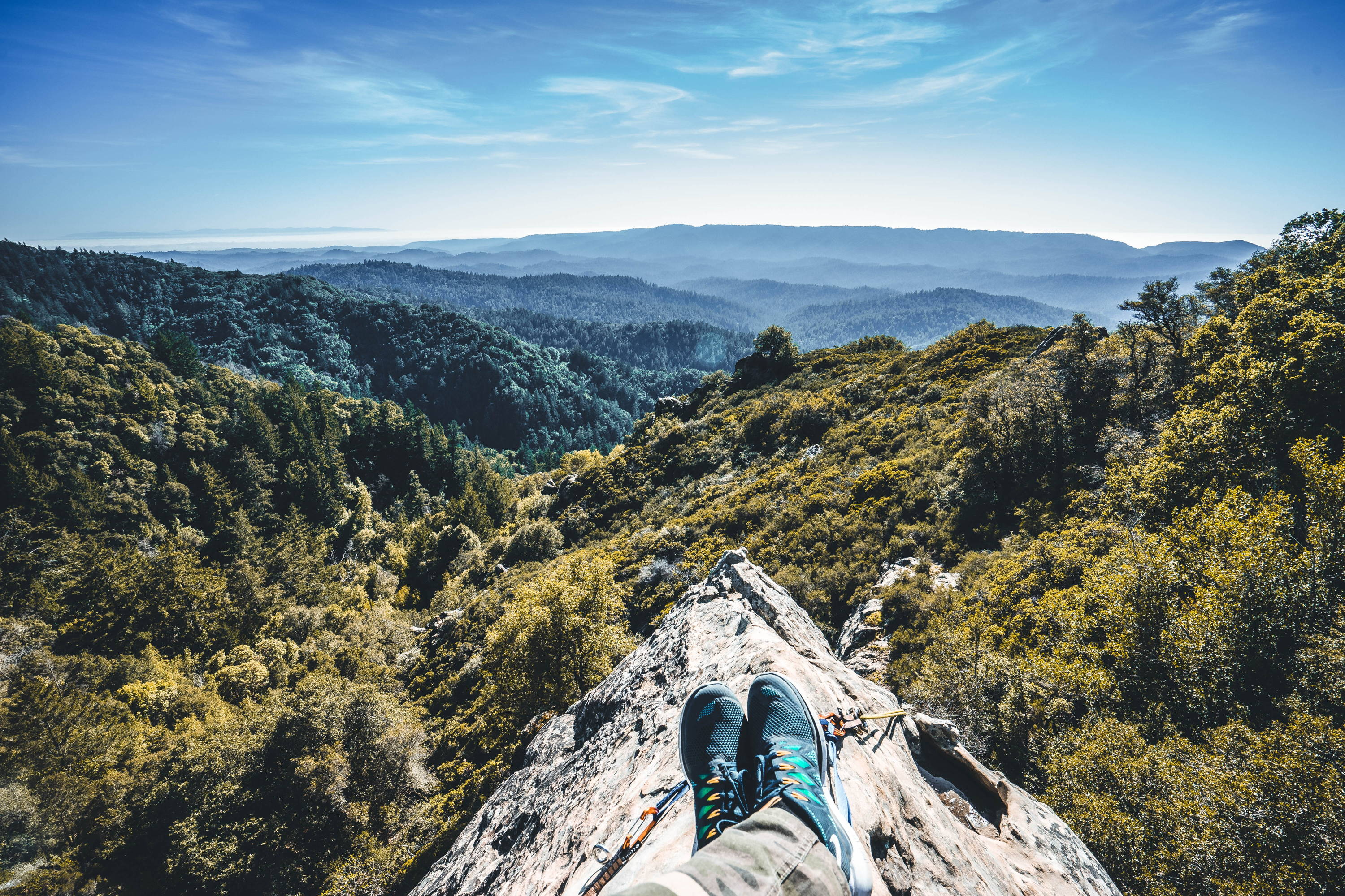 17 Best Backpacking Hacks for 2019 & Beyond. Man sits on rock with only shoes visible, overlooking lush, green valley below.