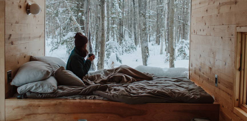 woman in bed sipping coffee looking at snow
