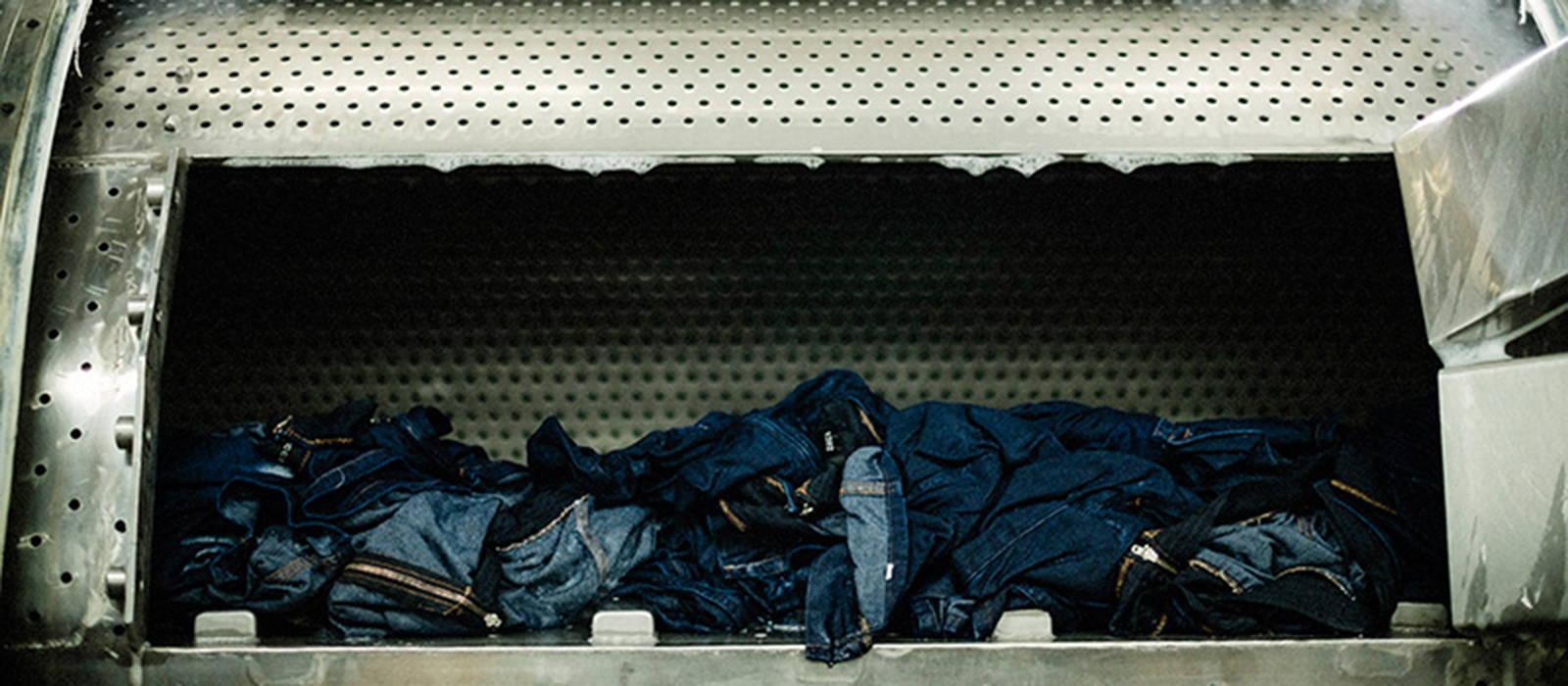 Pile of Edwin Jeans in an industrial washing machine at a Japanese factory