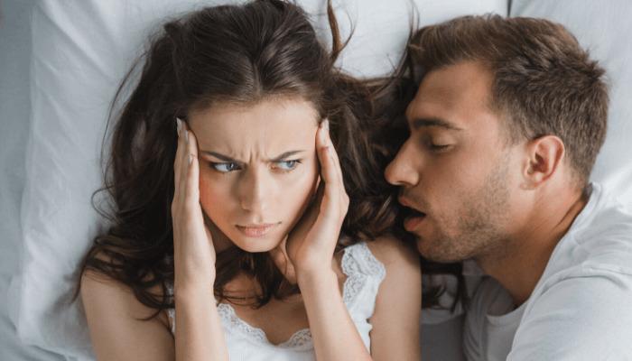 Frau ist genervt vom Schnarchen des Partners