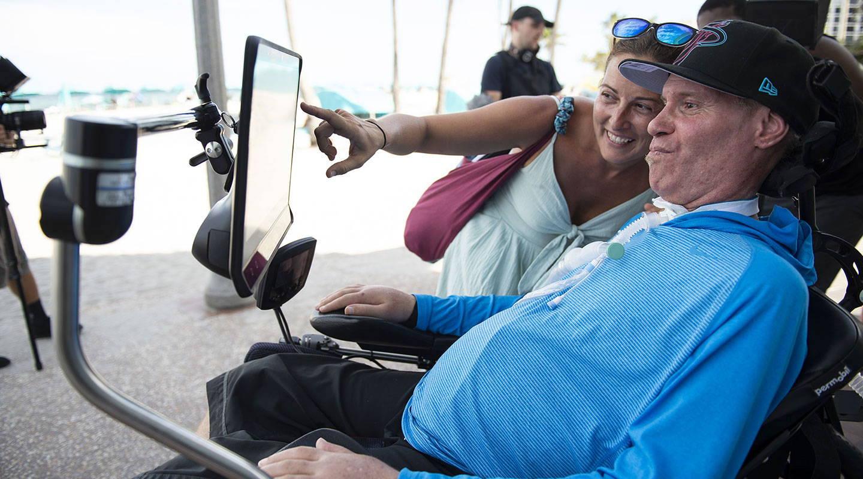 Mann benutzt ein UK-Gerät der I-Serie von Tobii Dynavox, um draußen zu kommunizieren