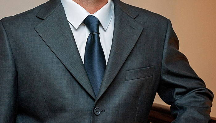 Man wearing a navy blue tie and gray suit