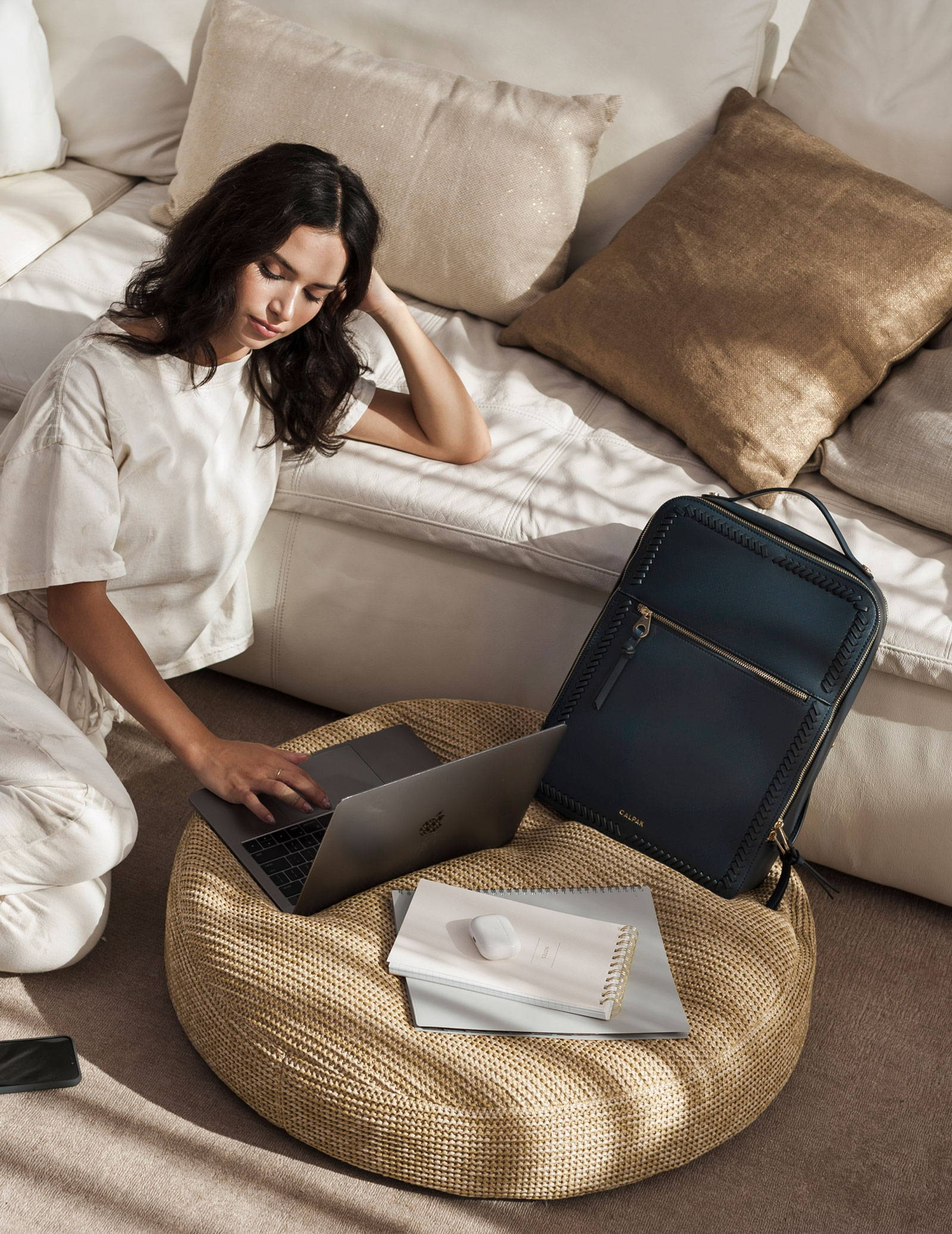 Model working at home with the Kaya Laptop Backpack