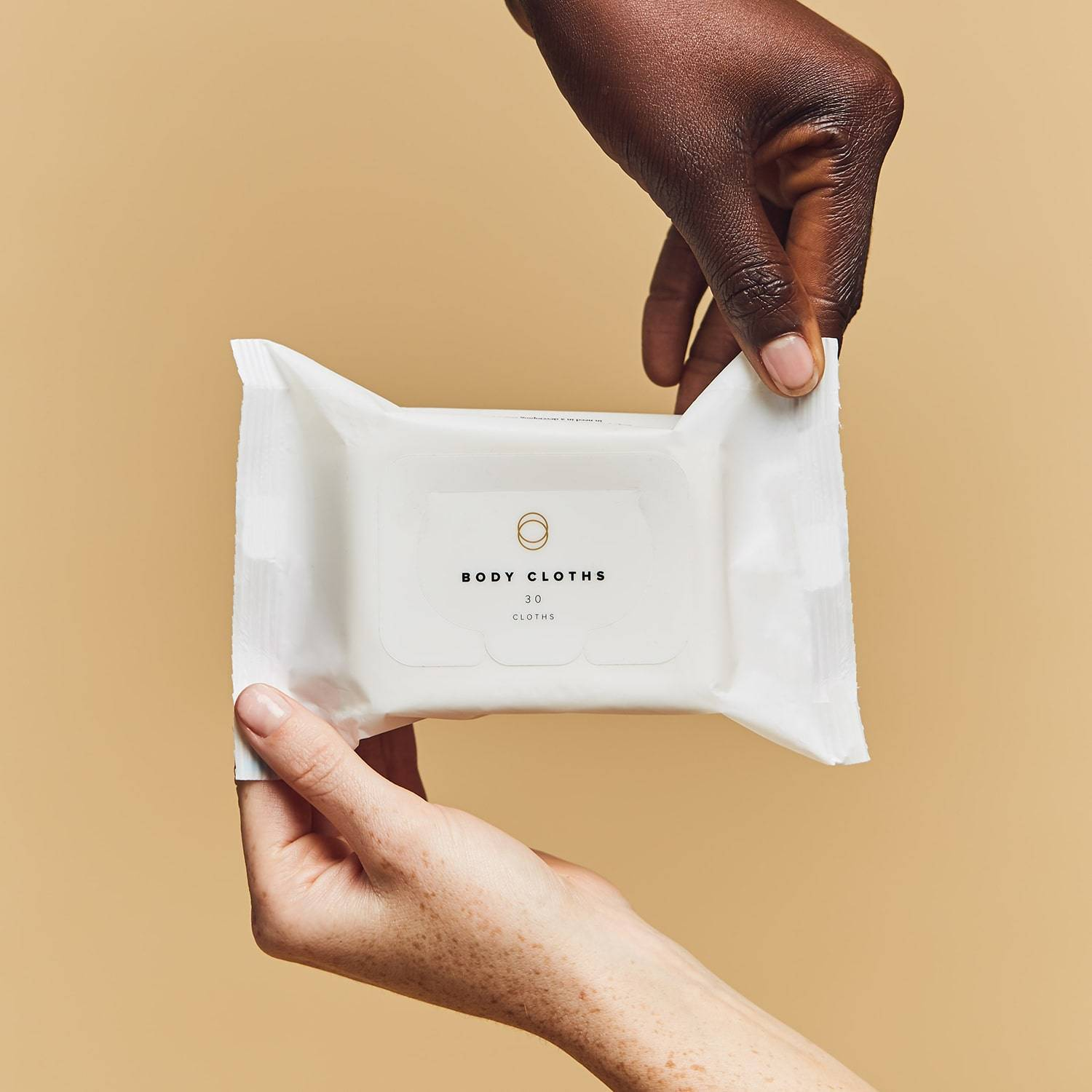 Two hands holding a pouch of body cloths