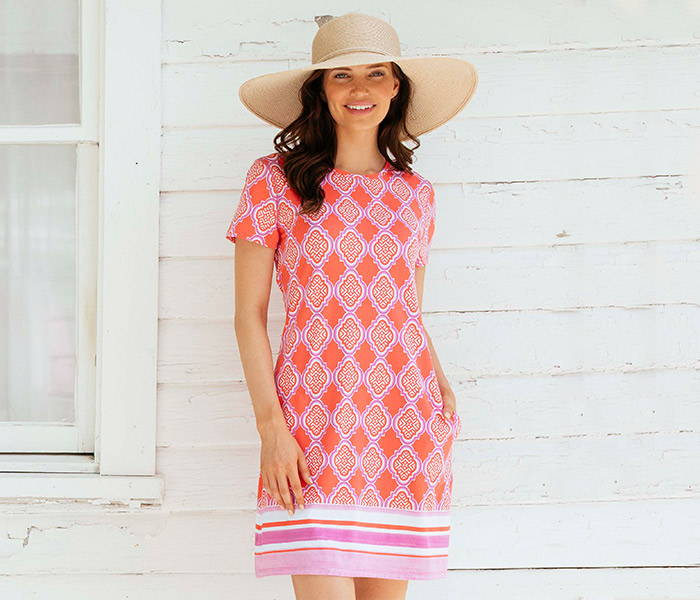 Woman wearing Coral Geo Cap Sleeve Swing Shift Dress with hat