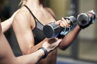 Frau macht Bizeps-Curls zur Vorbereitung auf Klimmzüge