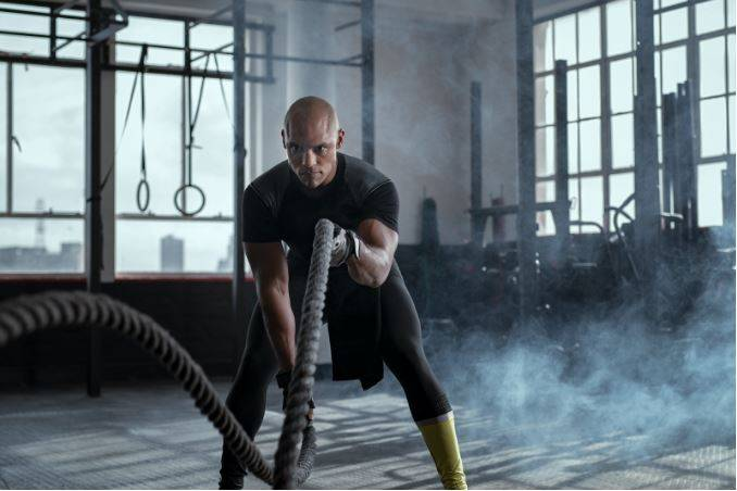 man using battle ropes|individual training vs group training|what is best for you