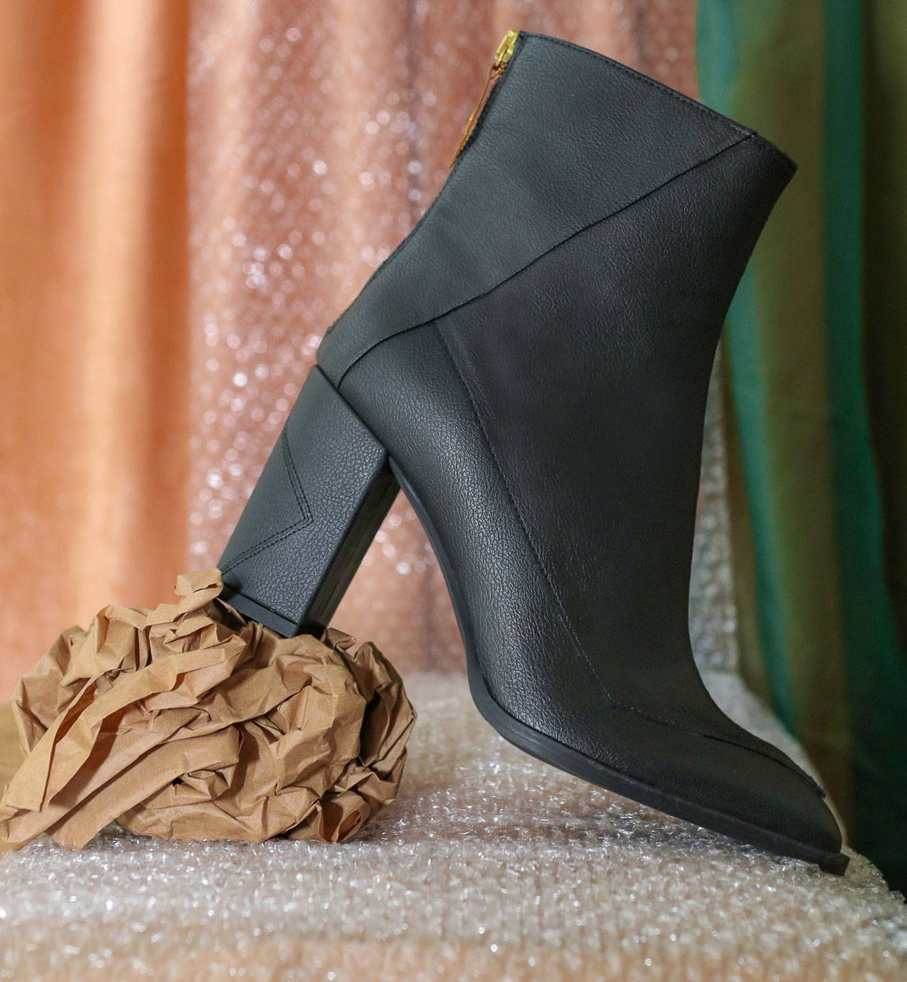 Sustainable vegan apple leather Almasi boot leaning on a piece of recycled paper and in front of a recycled backdrop