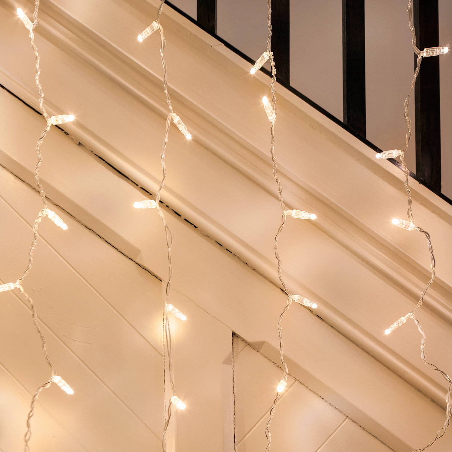 A close up of warm white led curtain lights hanging over a banister