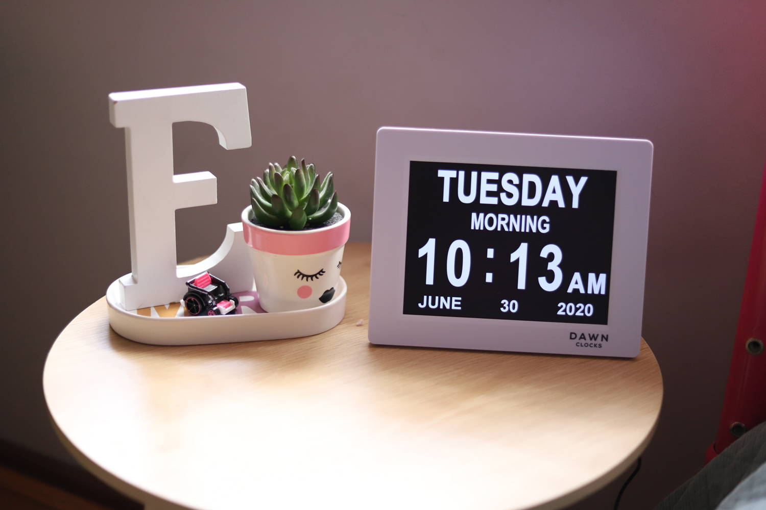 "Dawn Clock sits on bedside table next to white ""E"" and cactus."