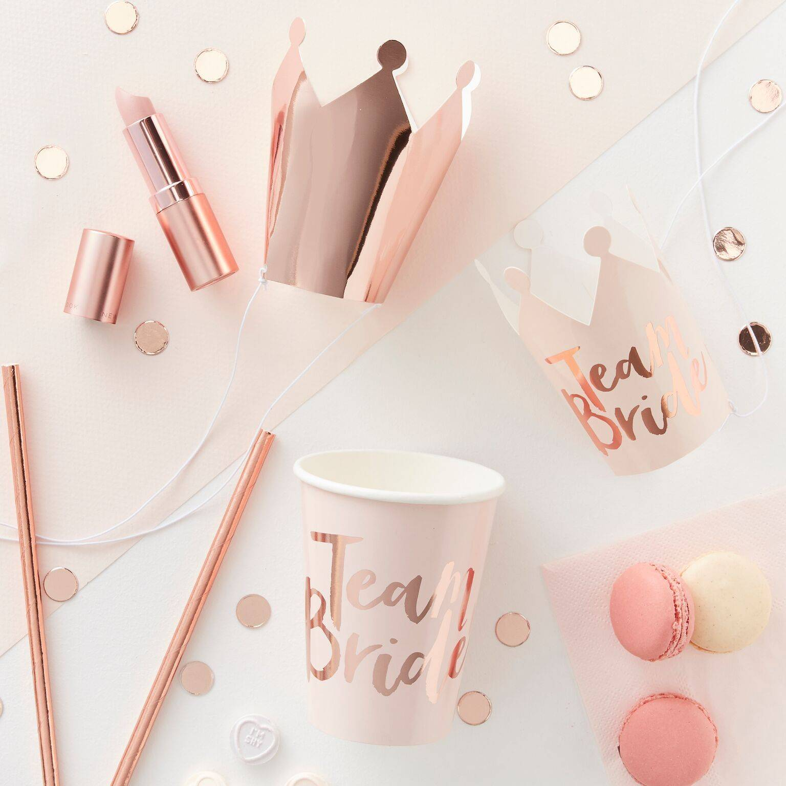 A flat lay photo of the Team Bride hen party collection including rose gold 'team bride' party cups, party crowns and hen party confetti for table decoration