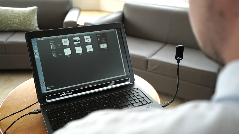 En mann bruker øyestyringsenheten Tobii Dynavox PCEye Plus til å få tilgang til den bærbare PC-en sin.