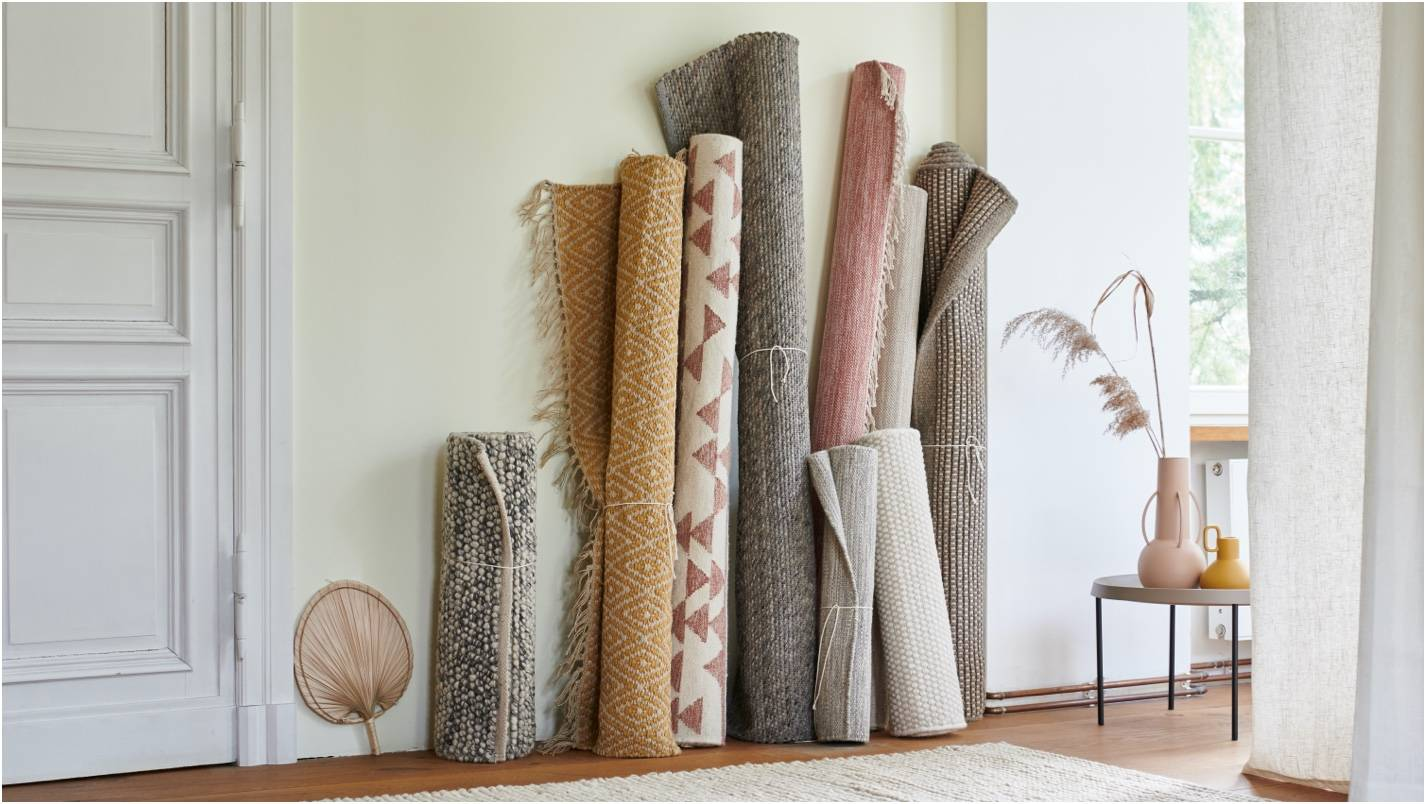Various patterned and textured rugs leaning against a wall. A clean, minimalist space.