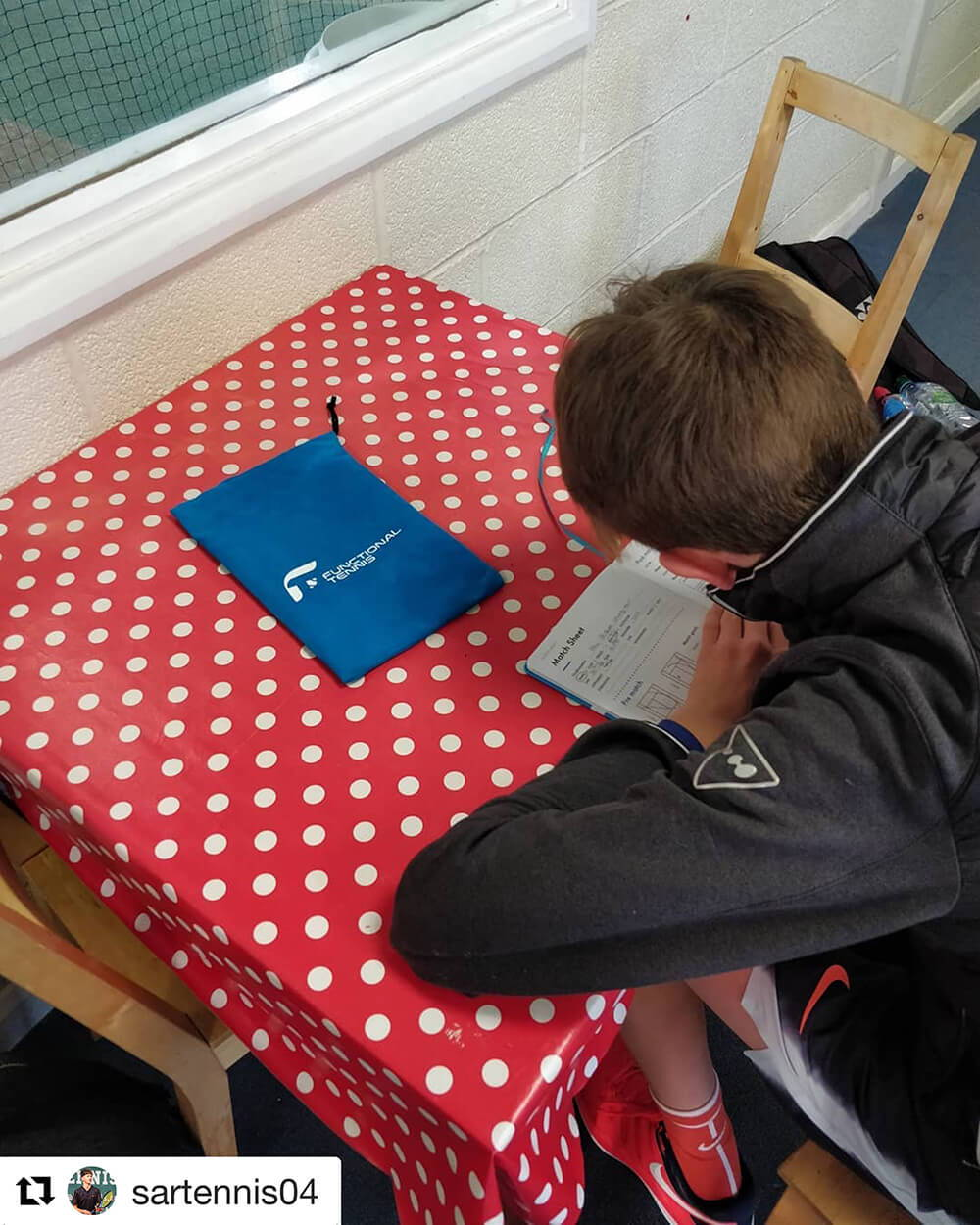 Sam writing down his match report with the Functional Tennis Journal
