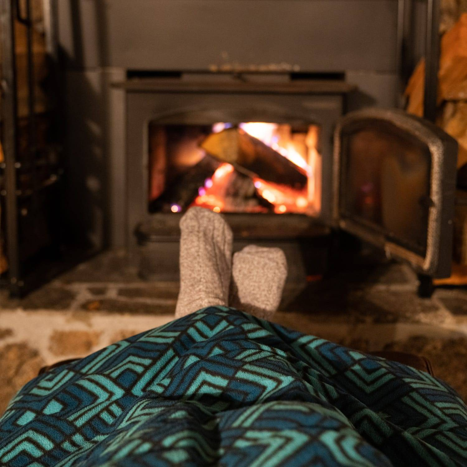 Legs under a throw blanket in front of a fire