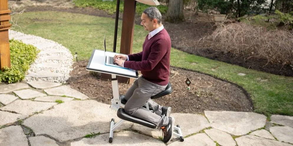 Man using The Edge Desk is the most adjustable ergonomic kneeling desk for the desk and back pain in his garden.