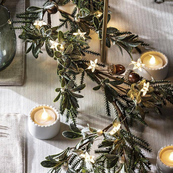 Star fairy lights entwined within garland as part of table centrepiece with LED tealights scattered on table