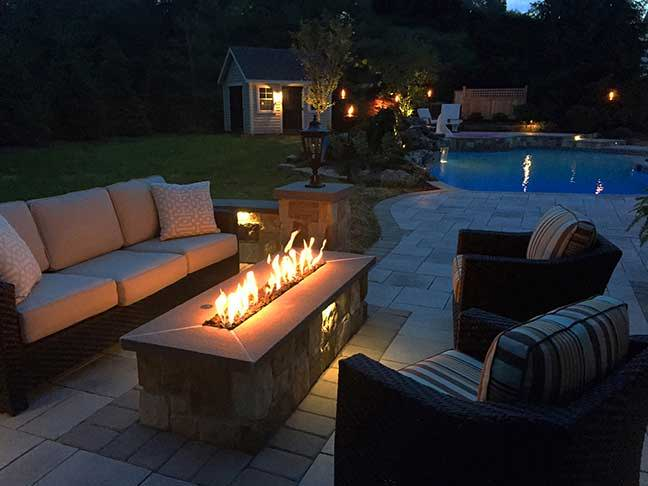 Deep seating couch and chairs  are placed around a stunning stone fire pit in a poolside backyard at evening.