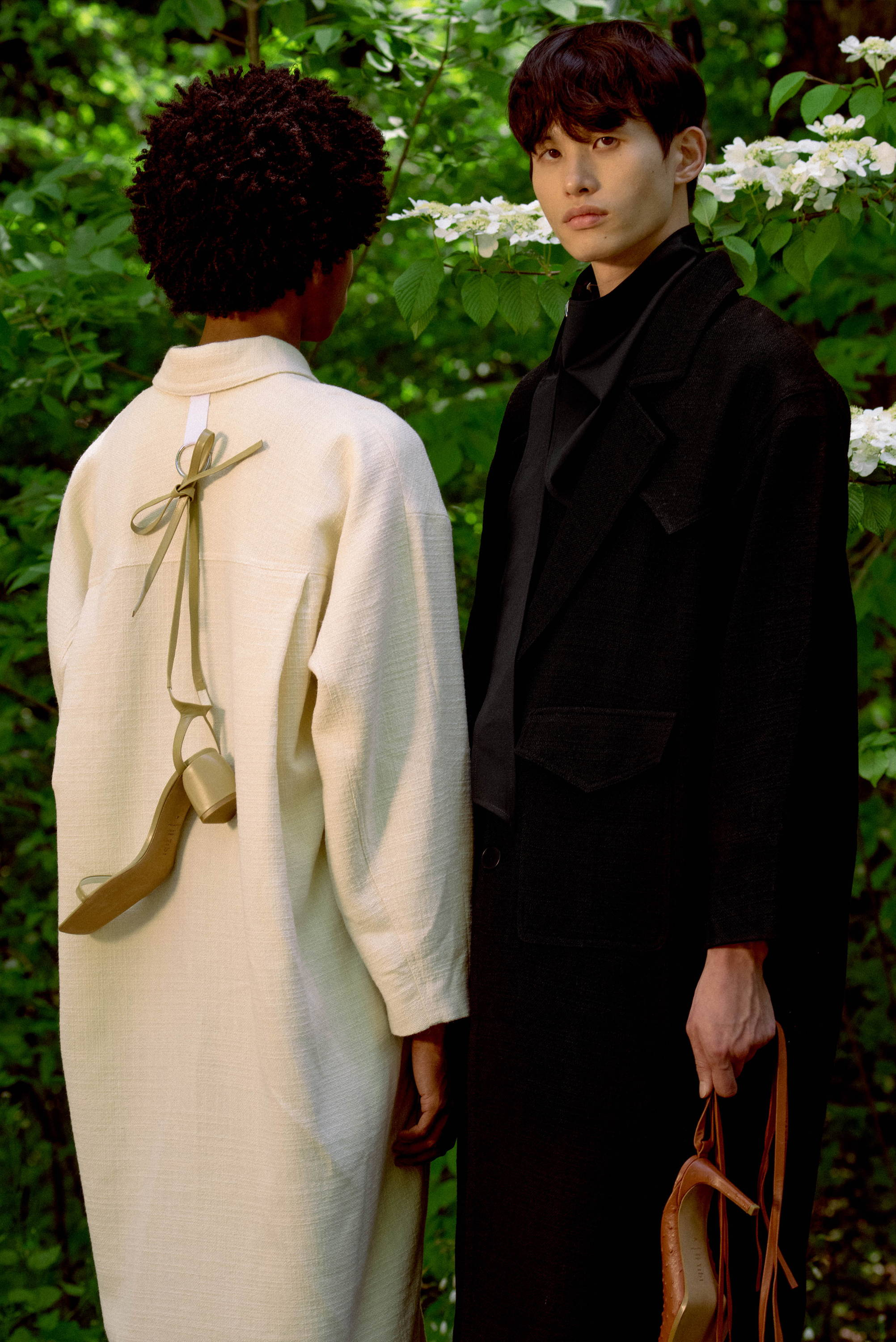 Male models wearing oversized coats. One model is facing away from camera with a shoe tied on his back.