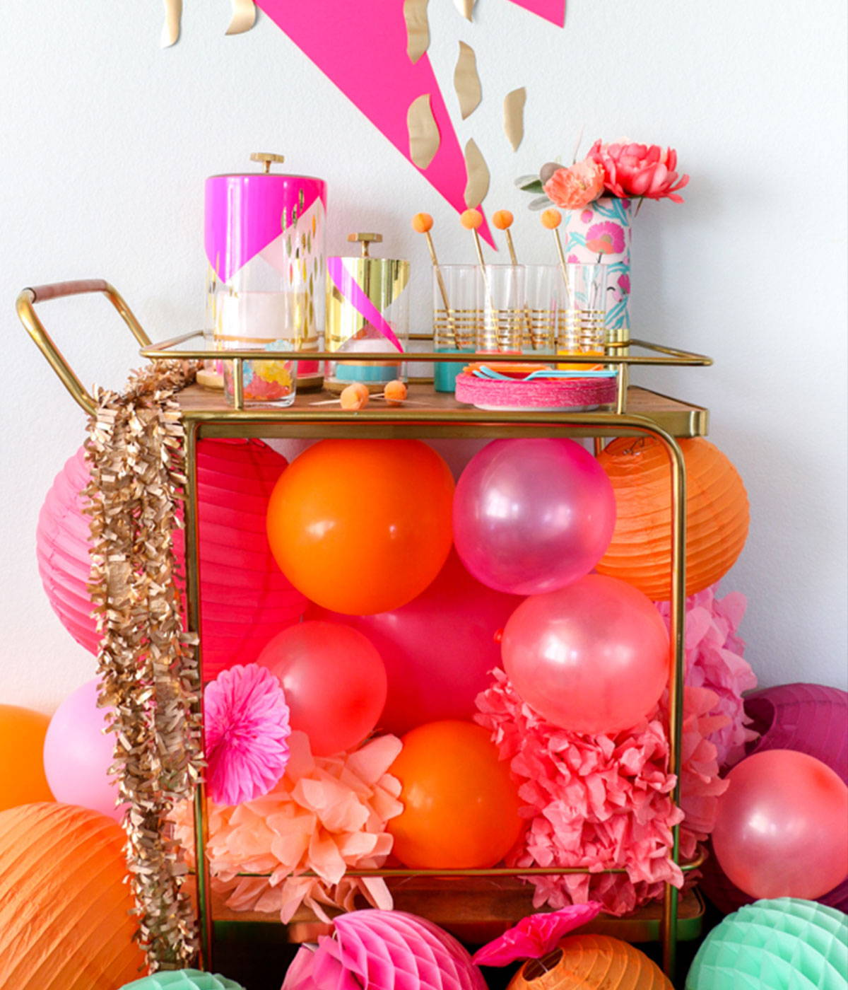 A festive gold barcart with balloons stuffed underneath the first shelf.