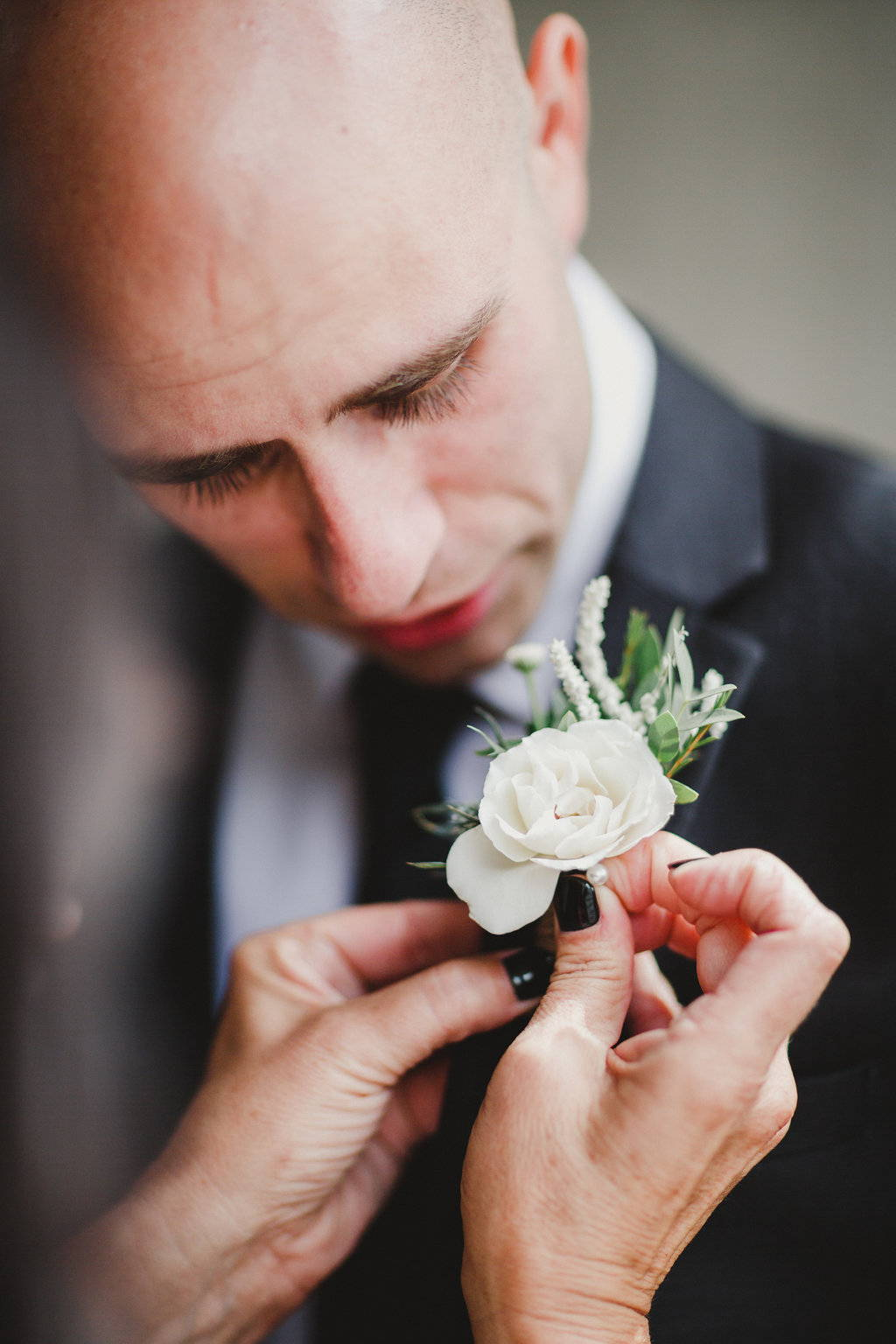 A groom with a boutonniere being pinned on him