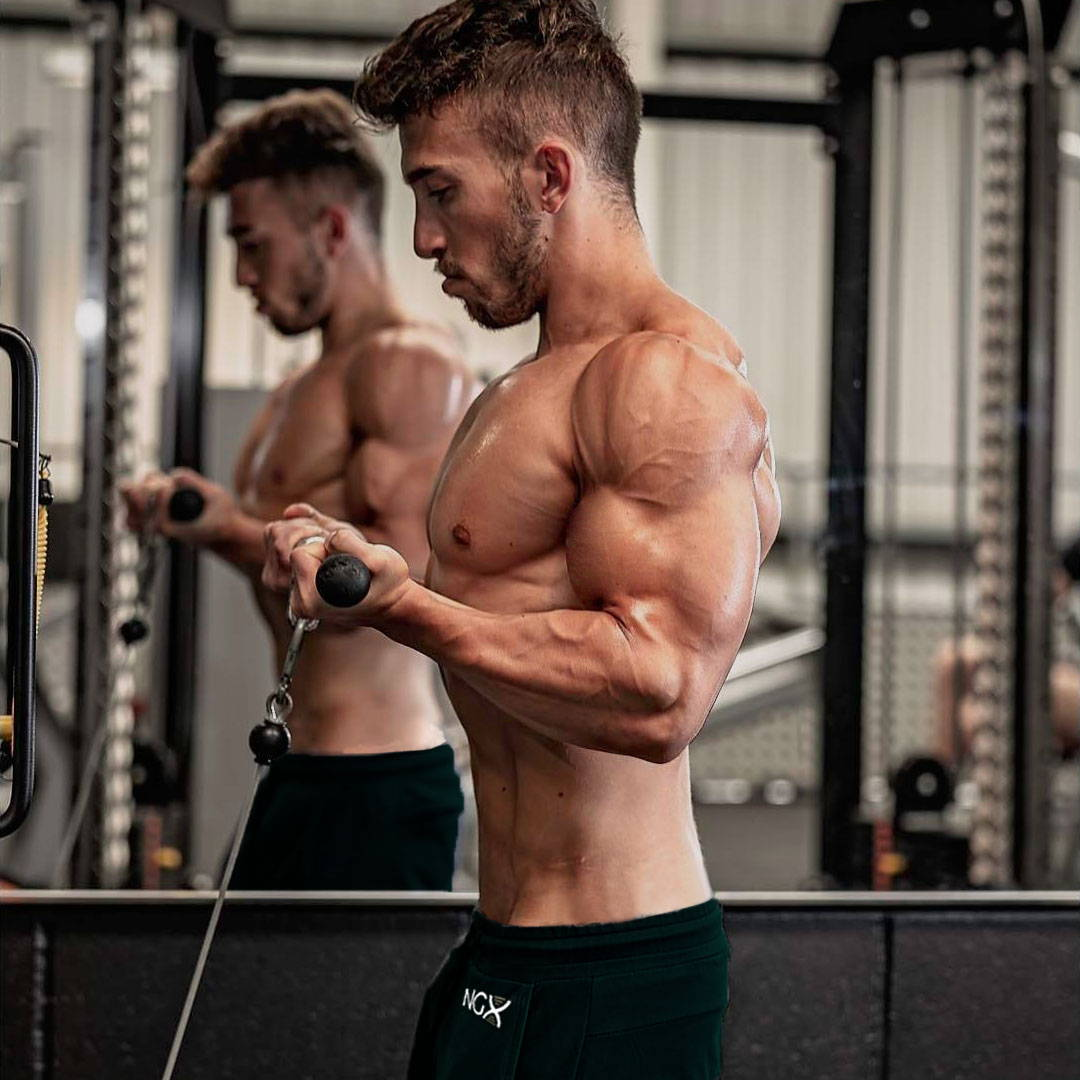 Tanned, muscular man curling a resistance bar in the gym