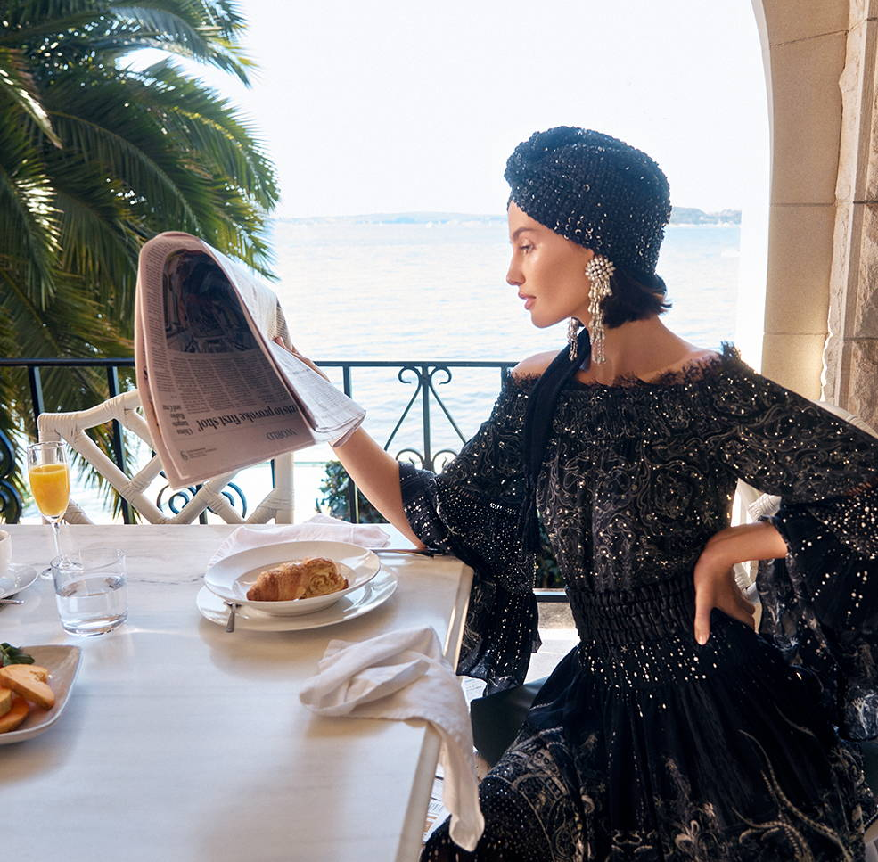 Model reading newspaper over breakfast in CAMILLA black and silver embellished off shoulder blouse and skirt with sequin turban.