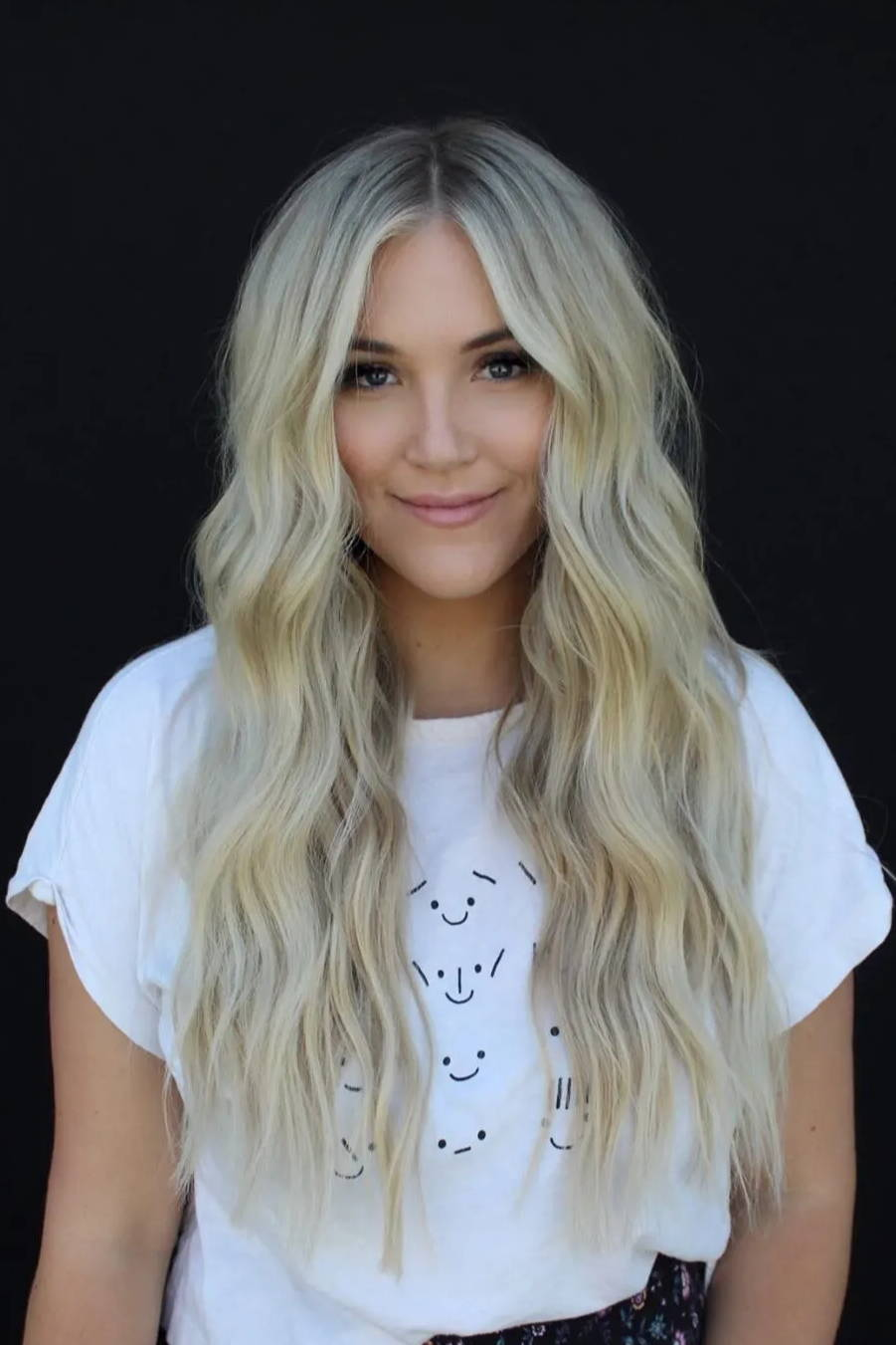 Beautiful women smiling and showing her platinum blonde hair extensions