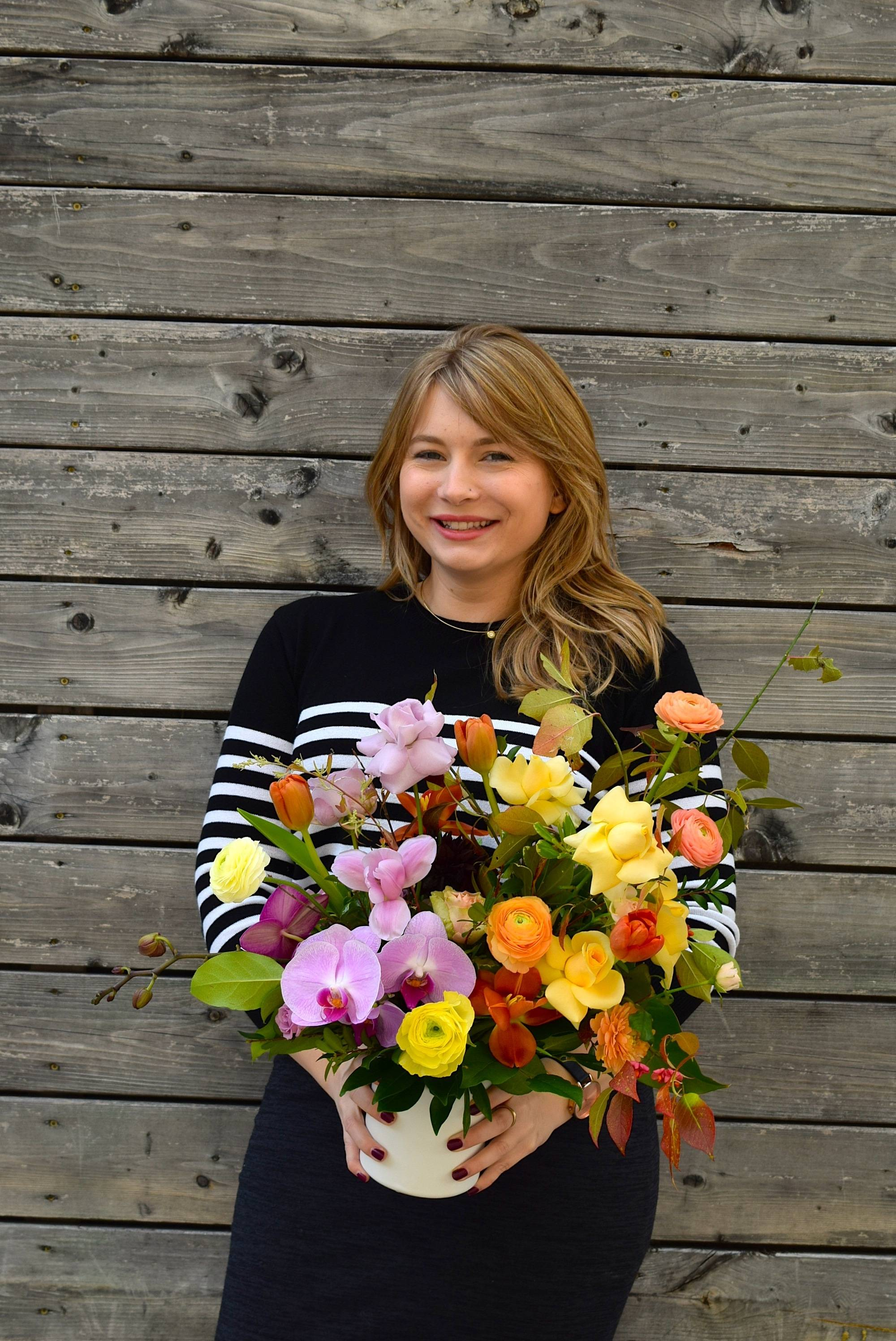 Jennifer Fowlow, Founder of Wild North Flowers holding a floral arrangement