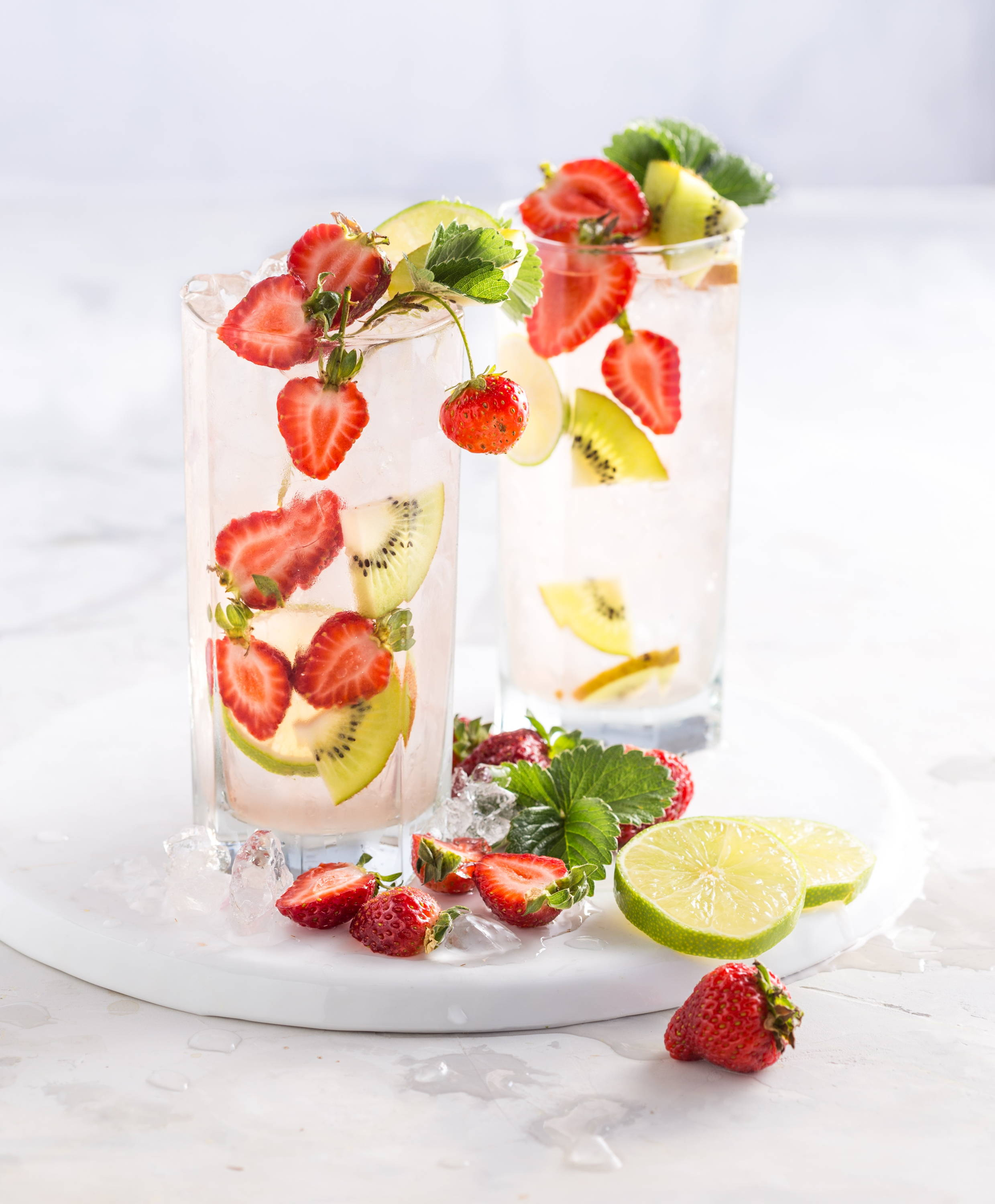 A glass of alkaline water infused with kiwis and strawberries