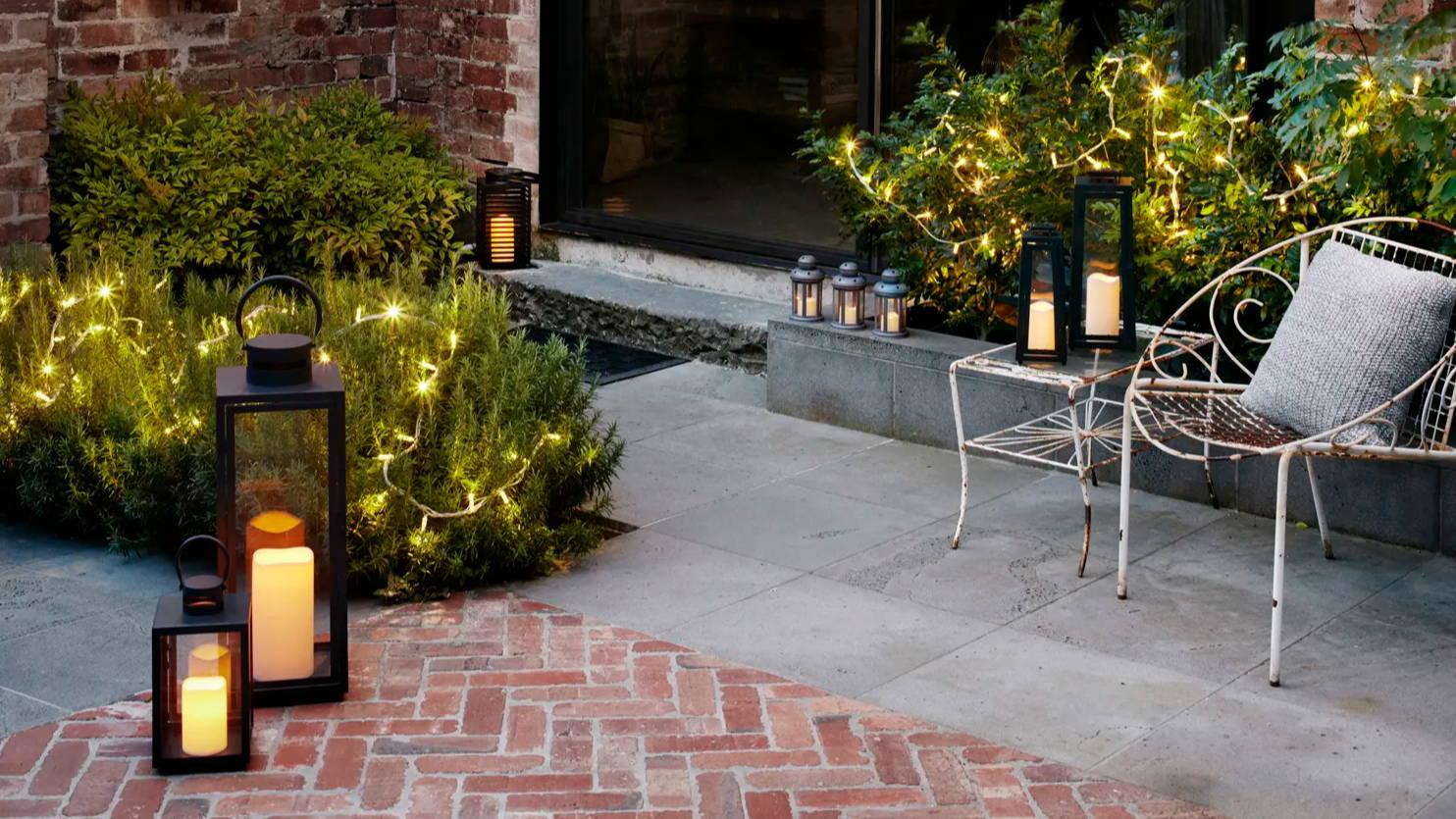 Patio with outdoor lanterns and fairy lights illuminated