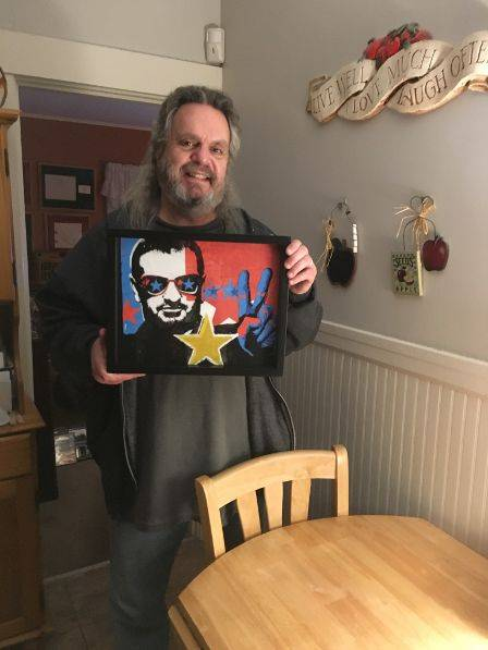 Shart Customer with framed Ringo Start Concert T-Shirt displayed in a Shart Original T-Shirt Frame
