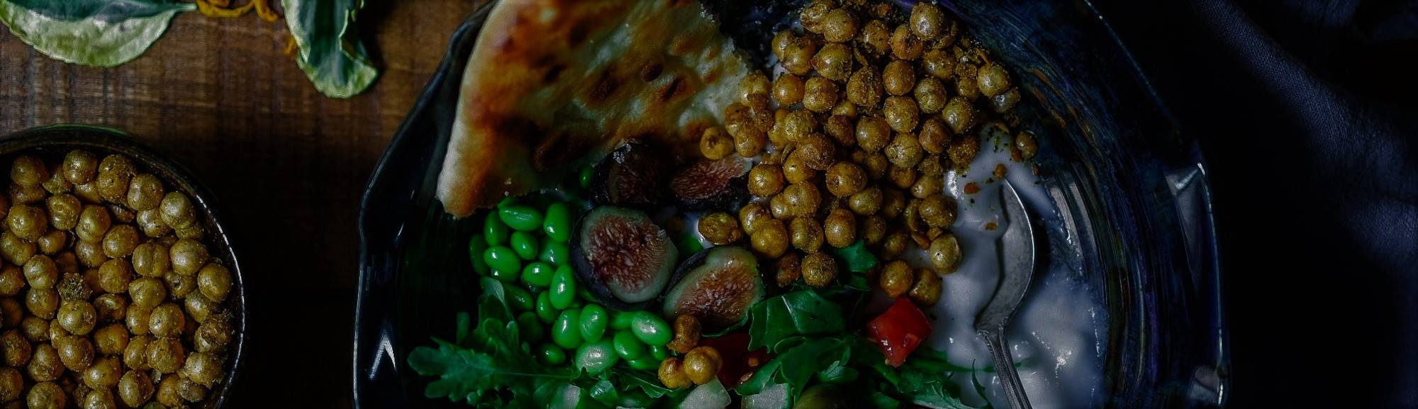 A vegan dish of chick pea, olives, fig, rocket and a naan bread