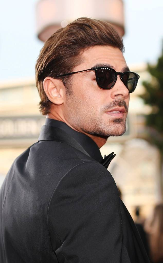 Zac Efron with pushed back brown hair and black sunglasses on