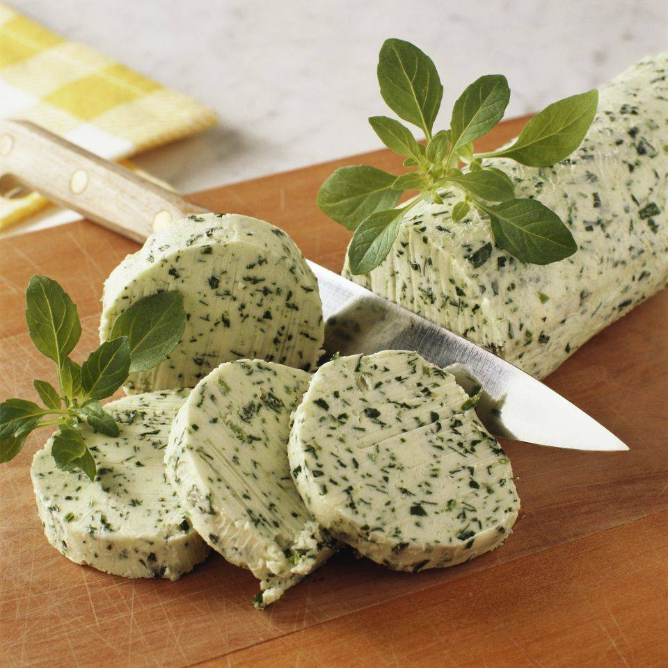 Knife cutting herb infused butter