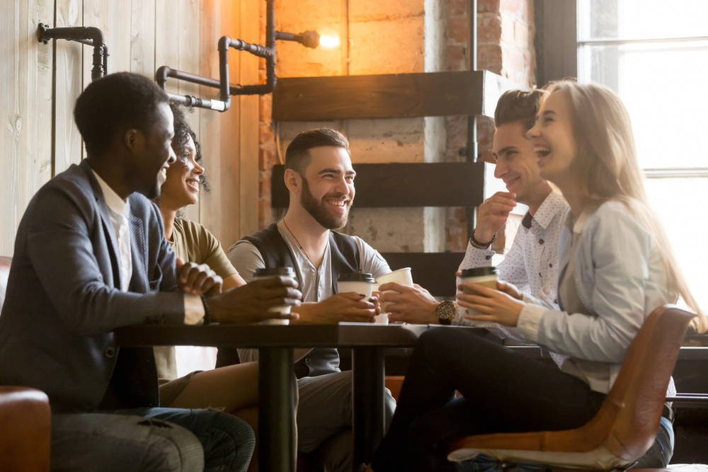 A group of friends is gathered around a table at a local coffee shop.