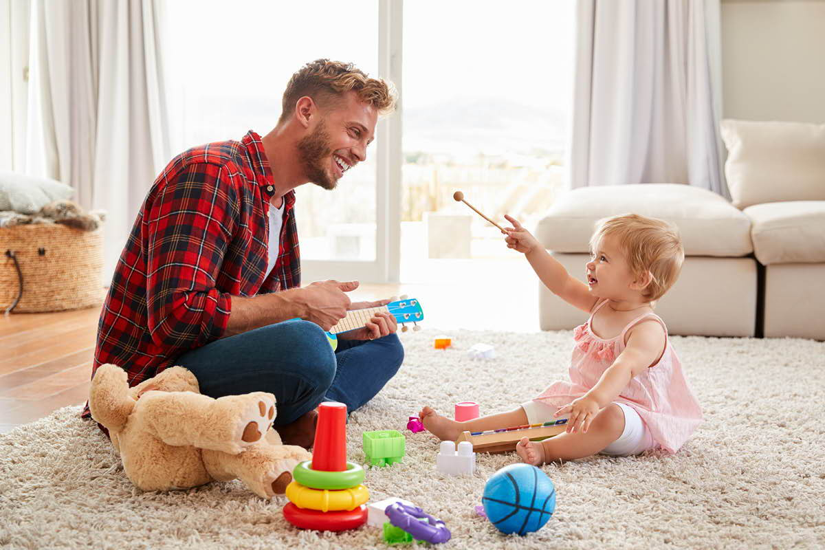 Father and daughter playing with musical toys on a cream shag rug.