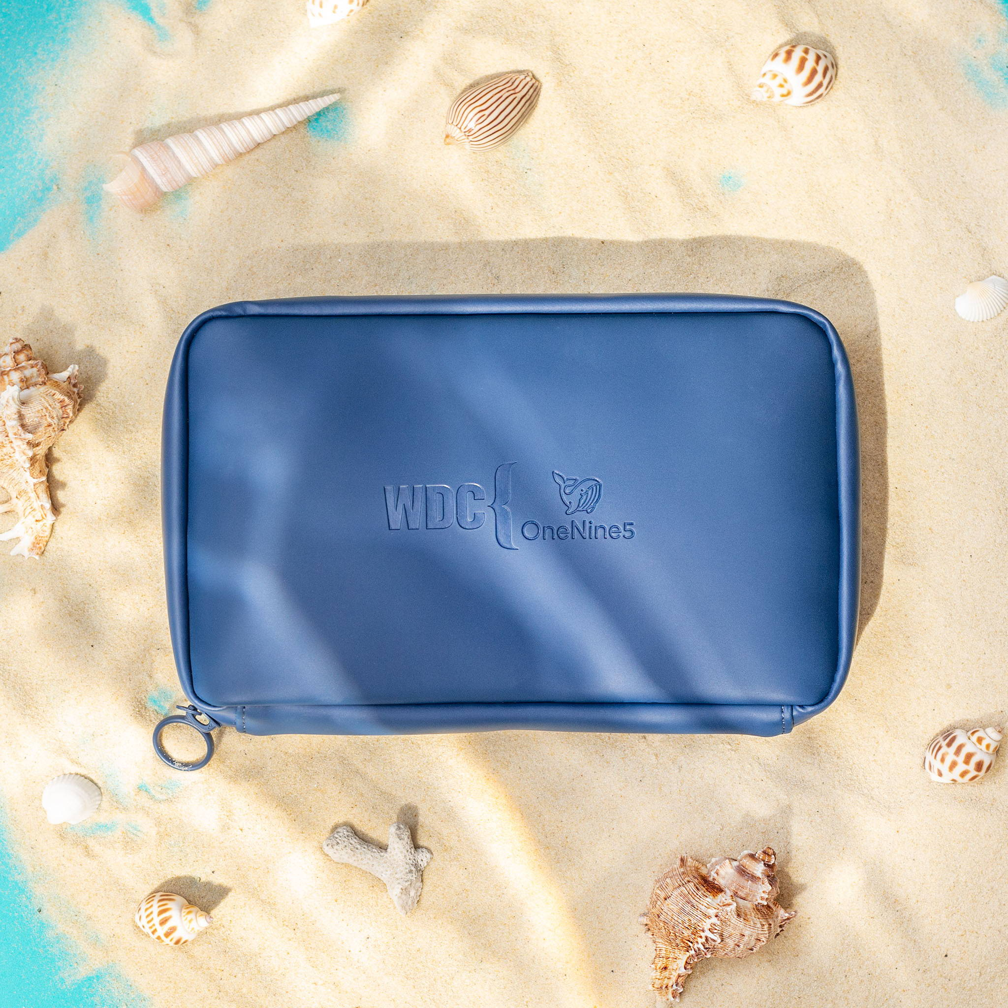 Birdseye image of the limited edition OneNine5 x WDC Eco Essentials Pouch. The blue pouch is surrounded by golden sand and shells to give a nautical feel.