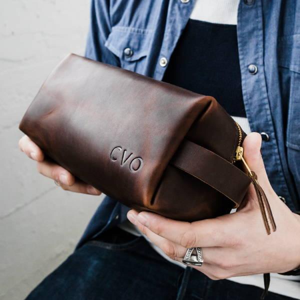 mens hands holding leather dopp kit