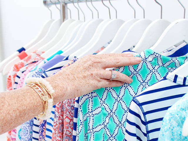 Hand touching clothing on a rack