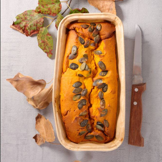 bright orange pumpkin loaf with sprinkled seeds on top on a table with leaves and a knife