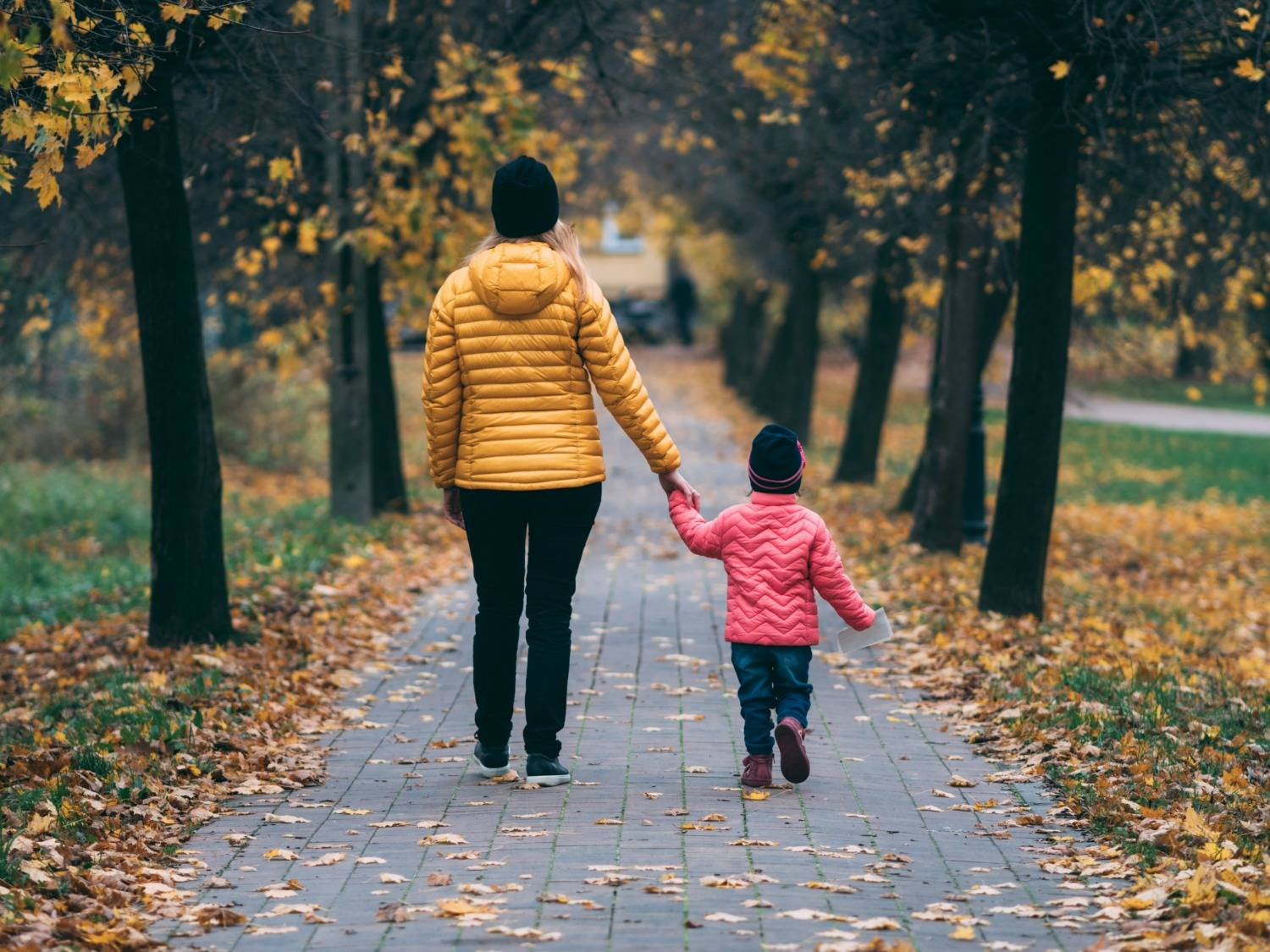 A Woman And Child Holding Hands Walking Through A Path Next To Autumn Trees
