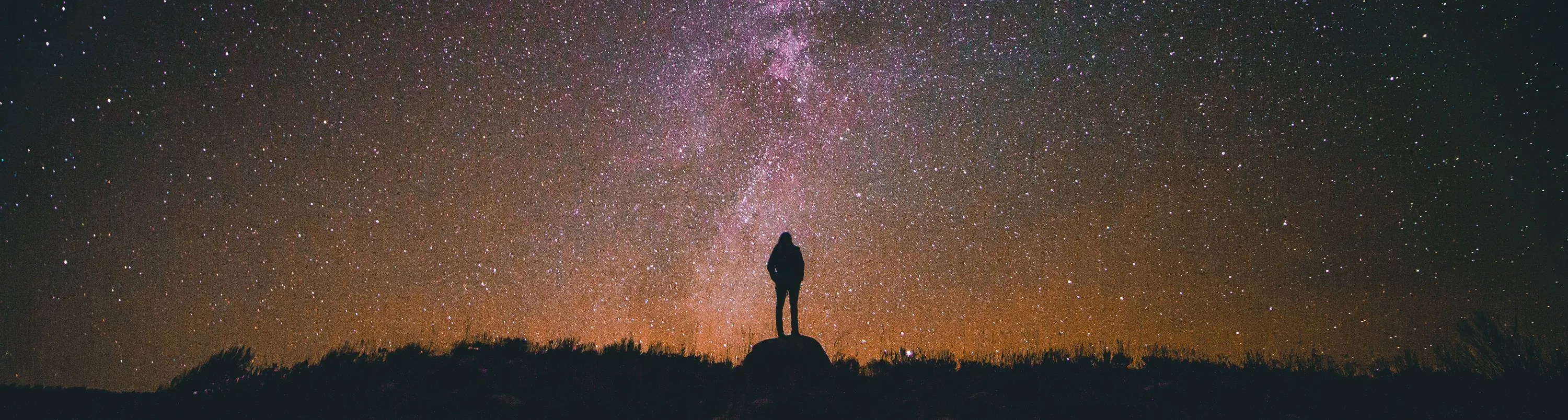 What is your carbon footprint Target? A man stands on a rock looking at a star filled  sky.