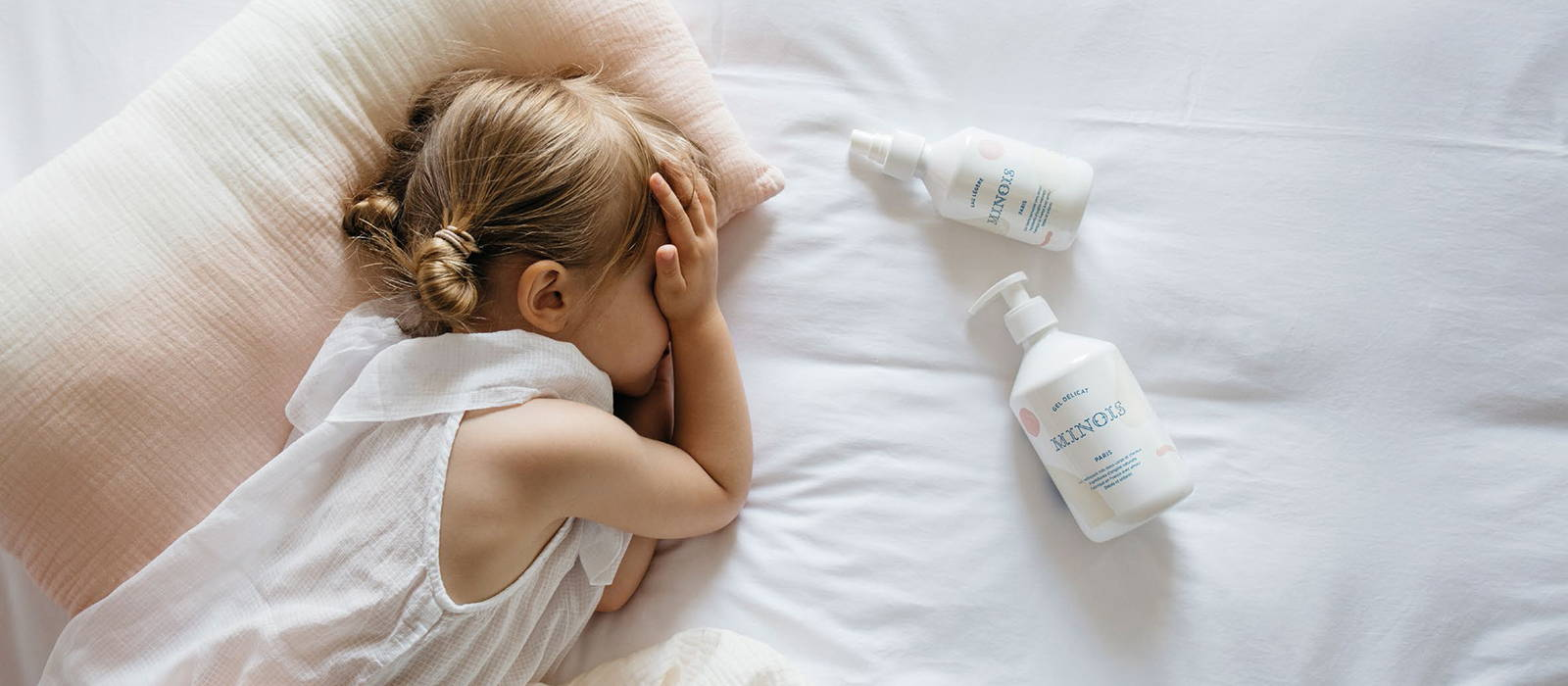Delicate Gels from Minois photographed alongside a small child lying down on linen. Minois Delicate Gel is sold at The Hambledon.