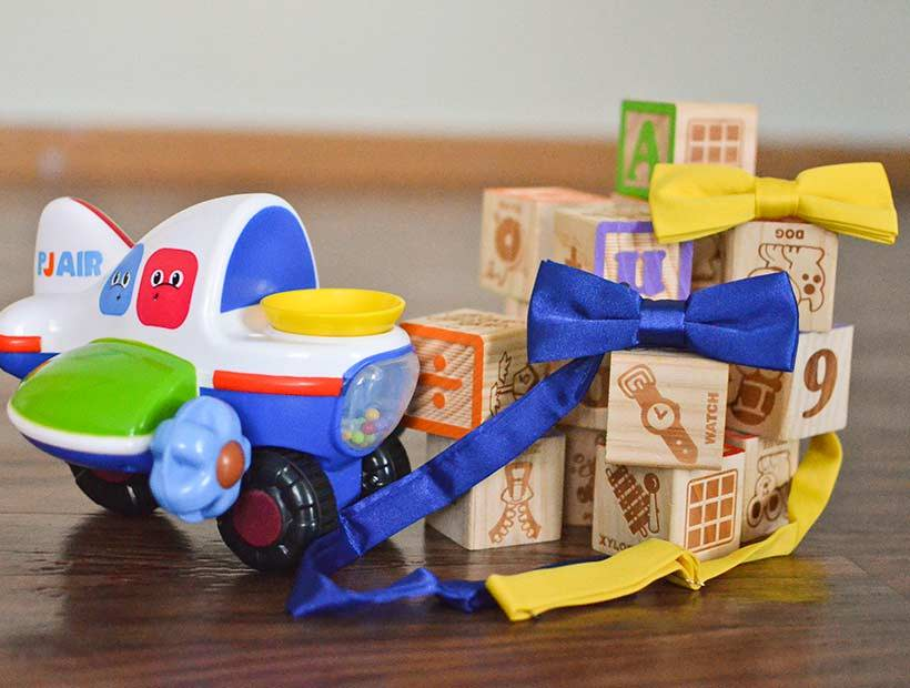 Boys' blue and yellow bow ties displayed among children's assorted toys